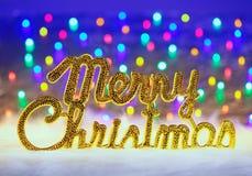 Frohe Weihnachten geschrieben in Gold mit Leuchten Lizenzfreie Stockbilder