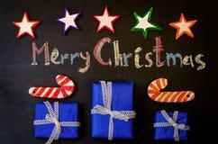 Frohe Weihnachten geschrieben mit Kreide auf einen schwarzen Hintergrund mit wo Stockfotos