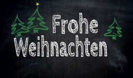 Frohe Weihnachten i tyskt svart tavlabegrepp för glad jul Arkivbild
