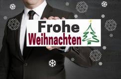 Frohe Weihnachten im deutschen Schild der frohen Weihnachten wird gehalten Stockbild