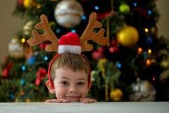 Frohe Weihnachten - Junge auf einem Weihnachtsbaumhintergrund Stockfoto