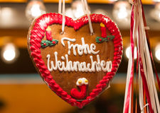 Frohe Weihnachten (Merry Christmas). Closeup of a traditional gingerbread heart at a Christmas Market, with the words Merry Christmas in German language Stock Image