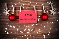 Frohe Weihnachten on a Red Banner in the Snow. The German Words Frohe Weihnachten, which means Merry Christmas, on a Red Label hanging on a Line in the Snow stock images
