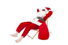 Frohe Weihnachten Santa Claus, die auf einem Stuhl mit Geschenktasche sitzt Lizenzfreies Stockfoto