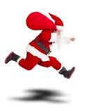 Frohe Weihnachten Santa Claus, die Geschenktasche und -betrieb hält Lizenzfreie Stockfotos