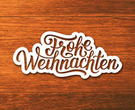 Frohe Weihnachten text on label. Christmas card. Frohe Weihnachten deutsch text on white paper label with hand lettering over wooden background. Merry Christmas Stock Photos