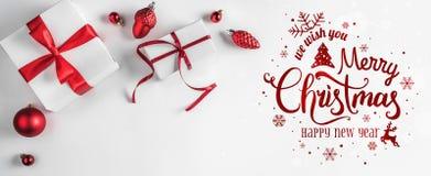 Frohe Weihnachten typografisch auf weißem Hintergrund mit Geschenkboxen und roter Dekoration lizenzfreies stockfoto