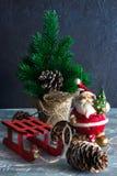 Frohe Weihnachten und ein glückliches neues Jahr Ein Santa Claus-Spielzeug, eine brennende Kerze und ein Pferdeschlitten glücklic stockfotografie