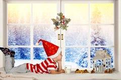 Frohe Weihnachten und frohe Feiertage! Ein kleines Kinderstillstehen, sitzend auf dem Fenster Wartesankt lizenzfreie stockfotografie