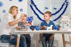 Frohe Weihnachten und frohe Feiertage! Mutter und zwei Söhne, die eine Schneeflocke malen Familie stellt Dekorationen für Weihnac stockfotografie