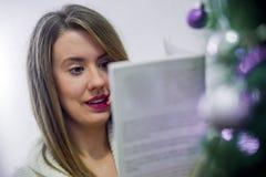 Frohe Weihnachten und frohe Feiertage! Recht junge Frau, die zuhause ein Buch nahe Weihnachtsbaum liest stockfoto