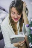 Frohe Weihnachten und frohe Feiertage! Recht junge Frau, die zuhause ein Buch nahe Weihnachtsbaum liest Weihnachten Lizenzfreie Stockfotografie