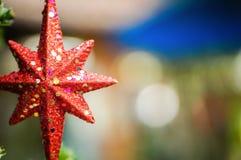 Frohe Weihnachten und frohe Feiertage roter Stern, unscharfer Hintergrund Stockfotografie