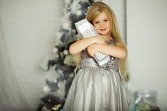 Frohe Weihnachten und glücklicher Feiertag Recht blondes Mädchen hält Weihnachtsgeschenk Lizenzfreies Stockfoto