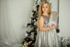 Frohe Weihnachten und glücklicher Feiertag Recht blondes Mädchen hält Weihnachtsgeschenk Stockfotos