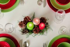 Frohe Weihnachten und guten Rutsch ins Neue Jahr! Тable, das festlichen Dekor - grüne und rote Teller, Kerzen und Tannenzapfen e stockbilder
