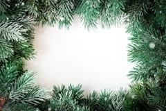 Frohe Weihnachten und guten Rutsch ins Neue Jahr Ein Rahmen von Tannenbaumniederlassungen auf einem weißen Hintergrund Hintergrun lizenzfreie stockfotos