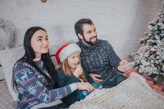 Frohe Weihnachten und guten Rutsch ins Neue Jahr Junge Familie, die zu Hause Feiertag feiert Der Vater hält die Direktübertragung stockbild