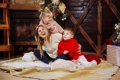 Frohe Weihnachten und guten Rutsch ins Neue Jahr Momand-Kinder, die Spaß nahe Weihnachtsbaum zuhause nahe Weihnachtsbaum haben lizenzfreies stockbild