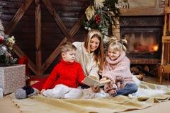 Frohe Weihnachten und guten Rutsch ins Neue Jahr Schöne Familie in Weihnachtsinnenraum Hübsche junge Mutter, die ein Buch zu ihr  stockfotos