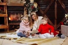 Frohe Weihnachten und guten Rutsch ins Neue Jahr Schöne Familie in Weihnachtsinnenraum Hübsche junge Mutter, die ein Buch zu ihr  lizenzfreie stockfotos
