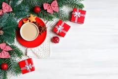 Frohe Weihnachten und guten Rutsch ins Neue Jahr Schale Kakao, Geschenke und Tannenbaumniederlassungen auf einem weißen Holztisch lizenzfreies stockbild