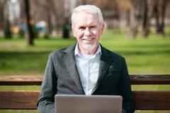 Froher älterer Geschäftsmann, der Arbeit genießt lizenzfreie stockfotografie