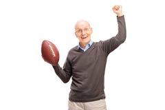 Froher älterer Mann, der einen amerikanischen Fußball hält lizenzfreie stockfotos
