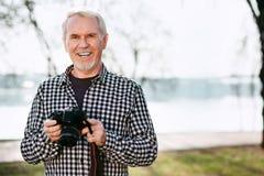 Froher älterer Mann, der Kamera nimmt stockbild