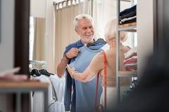 Froher älterer Mann, der stilvollen Pullover an seinem Kasten im Einkaufsspeicher hält lizenzfreies stockfoto