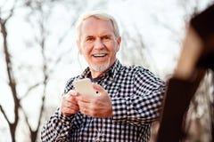 Froher älterer Mann, der Titelliste aufhebt stockfotos