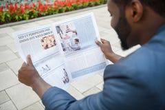 Froher afrikanischer Mann möchte Nachrichten kennen Stockbild
