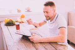 Froher attraktiver Mann, der zu Hause frühstückt stockbilder
