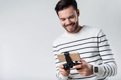 Froher bärtiger Mann, der tragbares gamepad lächelt und verwendet lizenzfreie stockbilder