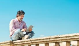 Froher bärtiger Mann mit digitaler Tablette draußen grasend zu seiner Frau Stockbilder