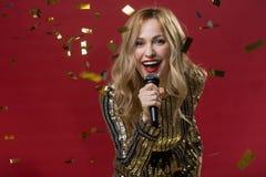 Froher blonder weiblicher Gesang in das Mikrofon Lizenzfreies Stockbild