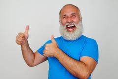 Froher gealterter Mann, der herzlichst lächelt und zwei Daumen aufgibt Lizenzfreies Stockfoto