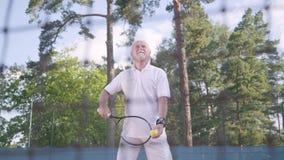 Froher glücklicher lächelnder reifer Mann, der Tennis auf dem Tennisplatz spielt Der alte Mann wirft den Ball mit dem Schläger ak stock video