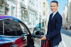 Froher höflicher Mann, der auf den Autositz zeigt stockbilder