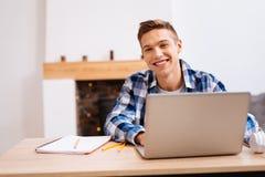 Froher Jugendlicher, der zu Hause seine Lektionen lernt Stockfoto