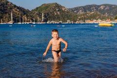 Froher Junge auf der türkischen Küste im Meer lizenzfreie stockfotos