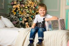 Froher Junge mit Geschenken nahe einem verzierten Baum Neues Jahr Stockfoto