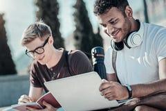 Froher junger Student, der einen Laptop verwendet stockbilder
