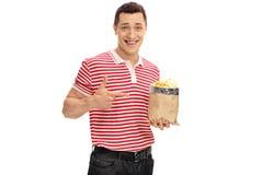 Froher Kerl, der eine Tasche von Chips hält Stockbild