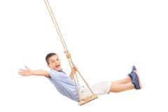 Froher kleiner Junge, der auf einem Schwingen schwingt stockfotografie