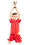 Froher kleiner Junge, der eine Trophäe über seinem Kopf hält Stockfoto