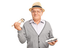 Froher älterer Herr, der ein Stück Sushi hält Stockfotografie
