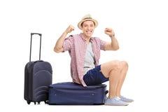 Froher männlicher Tourist, der auf seinem Gepäck sitzt Lizenzfreies Stockbild