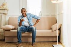 Froher Mann, der auf dem Sofa sich entspannt stockfoto