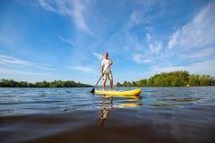 Froher Mann, der auf einem SUP-Brett auf großem Fluss schaufelt Lizenzfreies Stockfoto